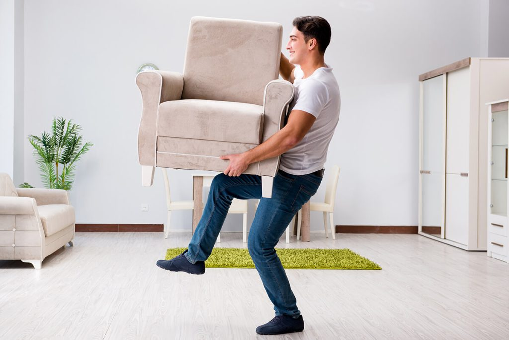 Guy carrying the armchair