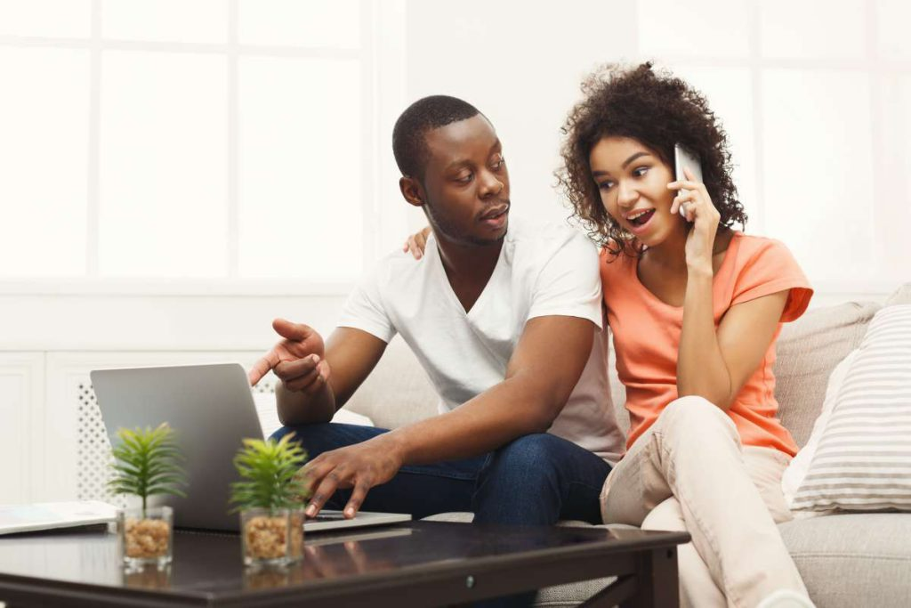 A woman and a man looking at the laptop, a woman calling to book the best movers in Dallas