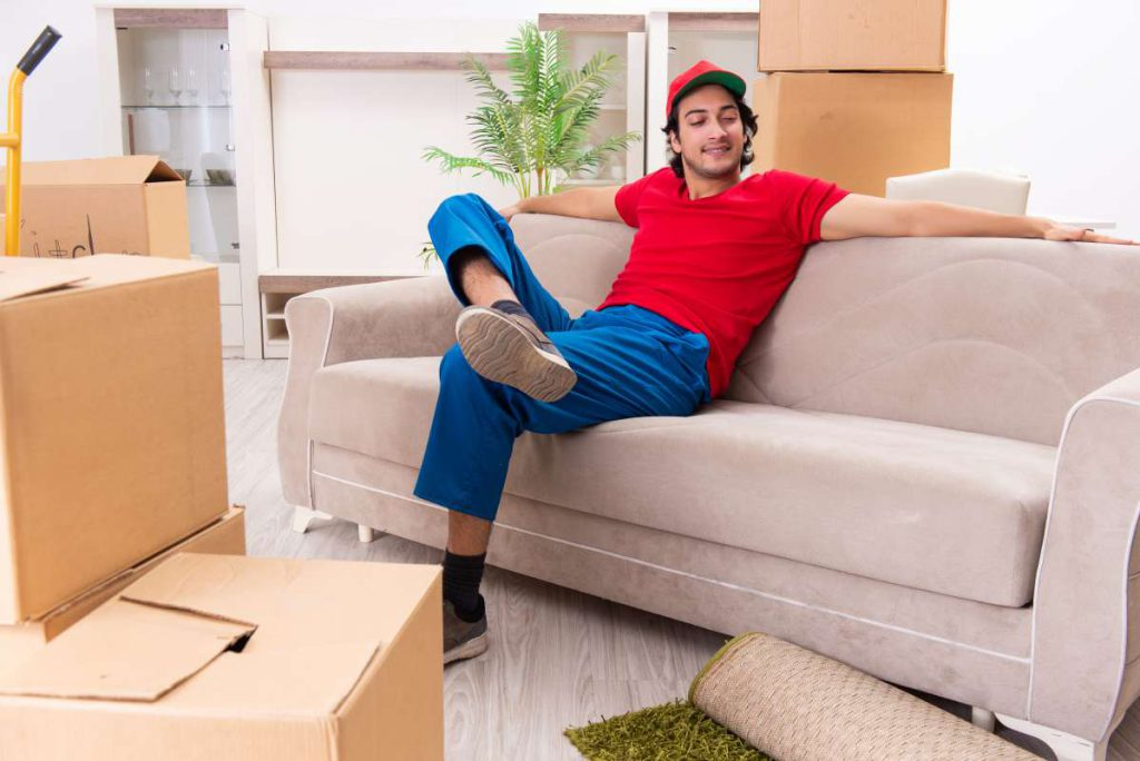 A smiling mover in Dallas, sitting on the sofa with his legs crossed