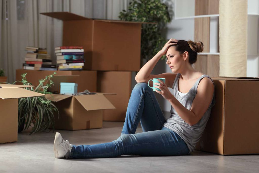 A girl sitting on the floor, holding her head, with a mug, surrounded by boxes